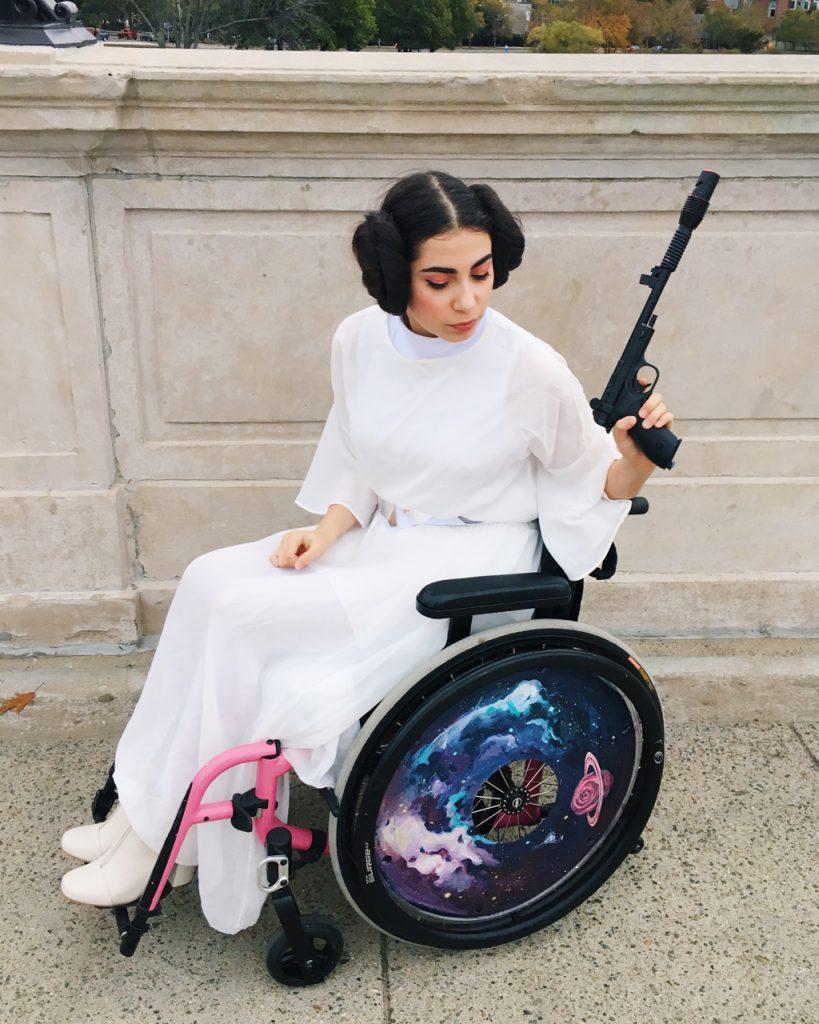 """Pildil on """"Star Wars'i"""" tegelaseks printsess Leiaks riietunud neiu pikas valges kleidis ja roosas ratastoolis, mille ratastele on maalitud galaktika."""